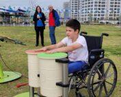 ילד יושב בכיסא גלגלים ומנגן בתופים בגן ציבורי